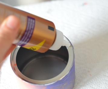 applying glue to rim of can for bird feeder