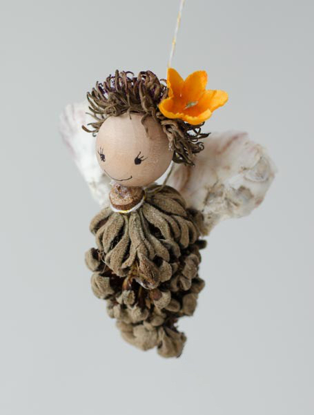 Nature fairy made from magnolia seed pod, wood bead, acorn top, and shells